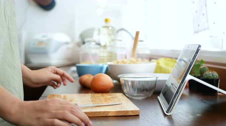 шалот : 4K. woman use finger slide on tablet screen, slice and peel a onion, prepare ingredients for cooking follow cooking online video clip on website via tablet. cooking content on internet technology Стоковые видеозаписи