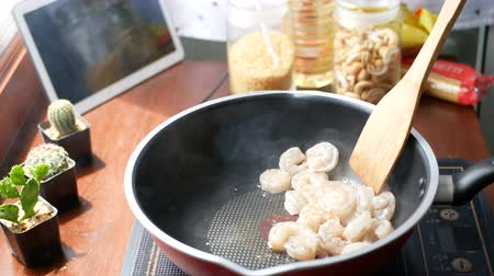 seafood recipe : 4K. female hand put the shrimp in a pan and stir, prepare ingredients for cooking follow. cooking content lifestyle concept