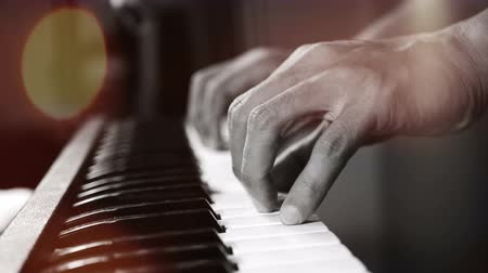 akord : 4K footage of music pianist hands playing piano at the night club with spotlight and light leak bokeh. musical instrument grand piano selective focus with depth of field
