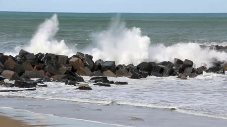 Waves breaking on the breakwater at high tide