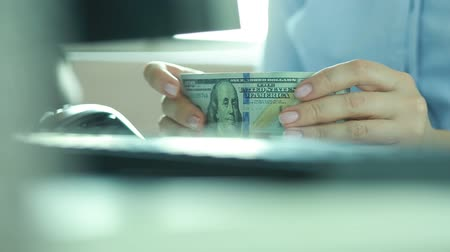 financování : Close-up of the hands of a business woman with a bundle of dollars. Fingers beat the rhythm of music.