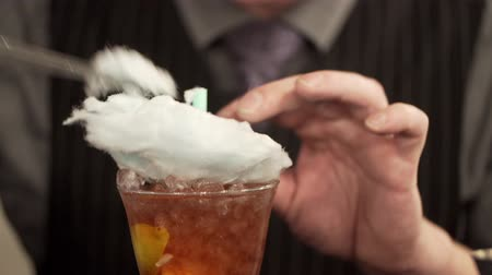 dissolução : Young man working as a bartender in a nightclub bar. The bartender decorates cocktail with cotton candy. Cotton candy is dissolved in cocktail. Cotton candy Stock Footage