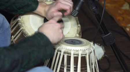 habitação : Close-up of man playing the tabla drum. A young man plays his djembe drum. Closeup mans hands drumming out beat on skin-covered bongo hand drum
