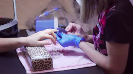 lakier do paznokci : Finger nail treatment, grinding and polishing in beauty salon. Manicure process in beauty salon, close up. Manicurist Hands Make Female Manicure With Nail Clippers In The Nail Salon.