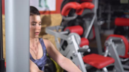 striving : Girl in the gym. Weight training. Work on the muscles of the back. Women working out on rowing machine in gym. Women on the exercise machine with a weighting compound. The woman lifts heavy weight in gym. Strong beautiful sports woman. Close up. Stock Footage