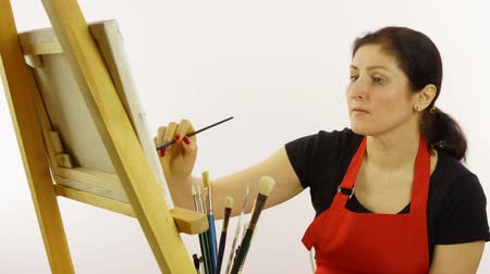 expressionism : Woman artist painting with paintbrush. The woman draws a picture. The artist on a white background draws on an easel oil paints. The woman in a red apron on a white background. Raznotsvtny picture paints. Close up