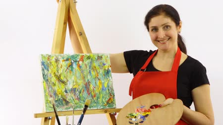 expressionism : The woman has stopped drawing a picture. The artist on a white background with an easel and oil paints. The woman in a red apron on a white background. Multi-colored picture paints. Close up