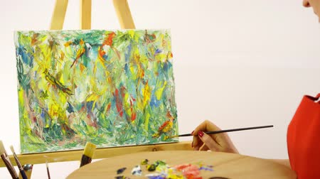 expressionism : Woman artist painting with paintbrush. The woman draws a picture. The artist on a white background draws on an easel oil paints. The woman in a red apron on a white background. Multi-colored picture paints.Close up Stock Footage