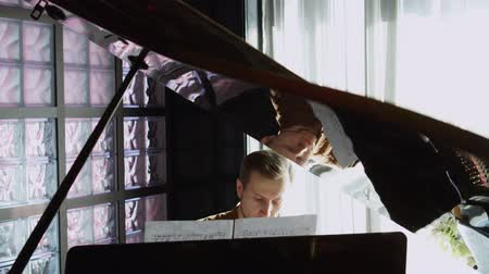 piyano : Playing piano. The young man plays a piano. The beautiful pianist plays melodies. Pleasant light from a window indoors. The Pproffesionalny pianist for a piano. Stok Video