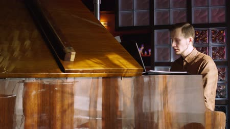 loção : Playing piano. The young man plays a piano. The beautiful pianist plays melodies. Pleasant light from a window indoors. The Pproffesionalny pianist for a piano. Stock Footage