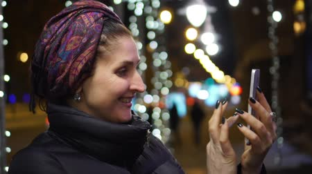 pic : The woman in brisk night time of day takes the picture on the smartphone on memory. The slow-motion shot of the woman
