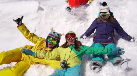 pojistka : Cheerful rest with friends in ski resort. Young girls I ride on snow from mountain top.