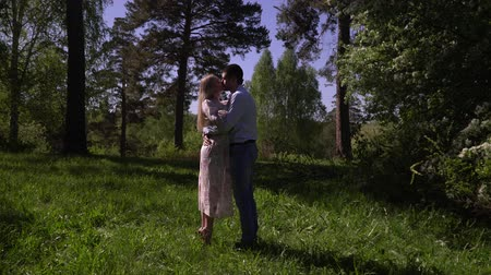 подростковый возраст : Young couple kiss on a tree in a garden. The beautiful girl with the guy dernutsya by hands on a glade