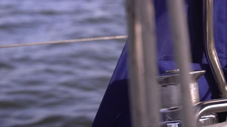 pulling rope : People sailing, man pulling ropes, winding sheets around winches. The yacht in the sea. Stock Footage
