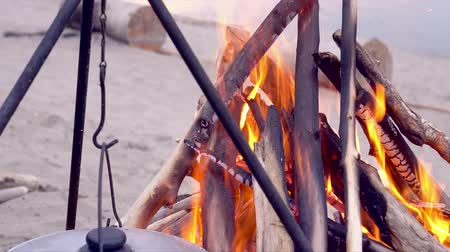 superior : A fire close up on the evening beach by the sea. On a fire the food in a copper is cooked Vídeos