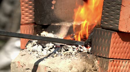 improvised : . The man mixes coals in a fire for forging threw. Coals in the improvised fireplace