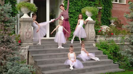 özel öğretmen : Little ballerinas train on a porch of ballet school with the teacher Stok Video