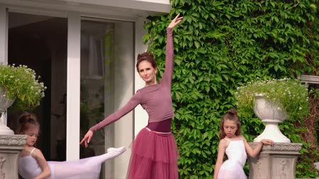 выполнять : Little ballerinas train on a porch of ballet school with the teacher. Beautiful ballerinas carry out exercises