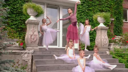 özel öğretmen : Little ballerinas train on a porch of ballet school with the teacher. Beautiful ballerinas carry out exercises on an extension before the ballet on a porch of school Stok Video