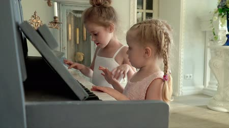 ballroom : Two little girls play the piano. Two little fair-haired girls learn to play the piano