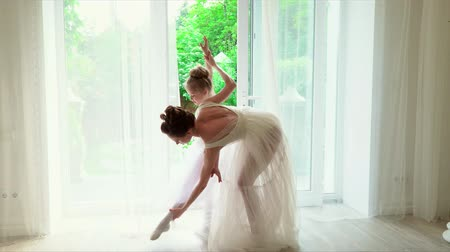 ballroom : The teacher of the ballet dances with the schoolgirls at a window. Beautiful ballerinas dance in a white ballet school. The senior ballerina is engaged with the schoolgirls individually. Lovely ballerinas in white ballet dresses. Darlings small in white p Stock Footage
