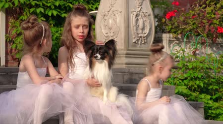tüt : Little ballerinas sit on a porch at school with a doggie Stok Video