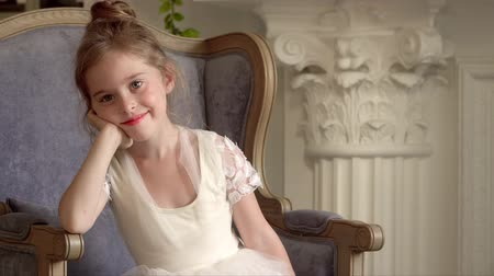 ballroom : The little girl sits in a big chair. Little ballerina field of occupations Stock Footage