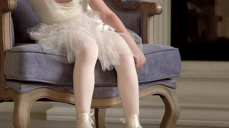 tüt : The little fair-haired girl sits on a chair at a fireplace in a white tutu. Legs of the little ballerina in white pointes. Legs close up