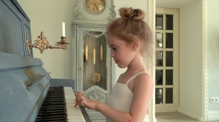 rajstopy : The beautiful little ballerina in a white tutu plays a synthesizer. The girl touches keys on a synthesizer..