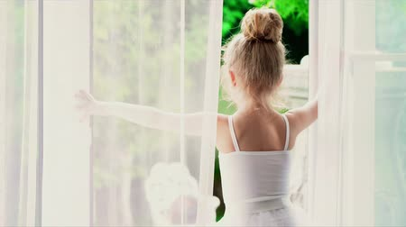 tüt : The beautiful little ballerina looks at the nature outside the window. The little girl in a white tutu is by the window. The little ballerina is by the big window with white curtains. Little cute girl..