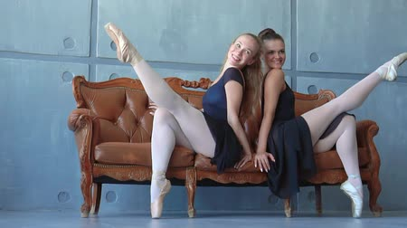 alıcı : Two girls in pointes sit on a sofa at ballet school. Beautiful ballerinas pose for a photo in studio of the ballet