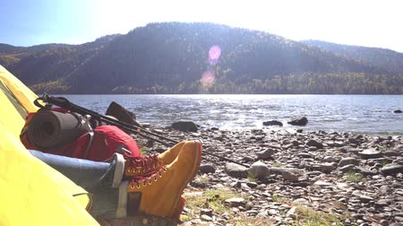 носок : Female legs in tourist boots in a yellow tent. Mountain lake. The female traveler costs ashore.