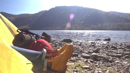 Female legs in tourist boots in a yellow tent. Mountain lake. The female traveler costs ashore.