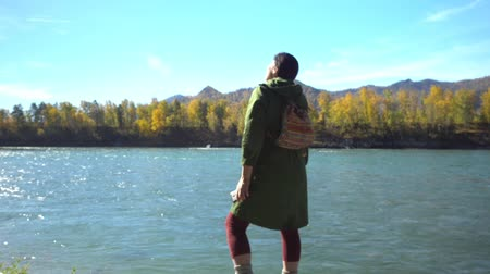 caneca : The female traveler on the bank of the mountain river.