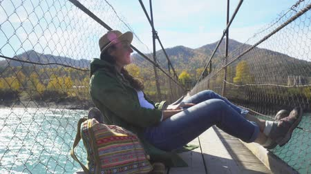 The female traveler on the suspension bridge through the mountain river. View of the river.