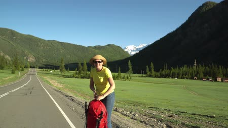 wet t shirt : The woman the traveler, with a red backpack, goes along the road. Mountain area. Bright sun, view of the snow mountain and of green hills.