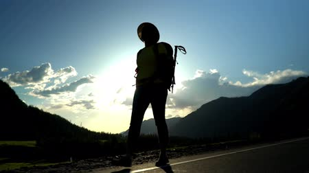 wet t shirt : The woman the traveler, with a red backpack, goes along the road. Mountain area. kontrovy light. Stock Footage