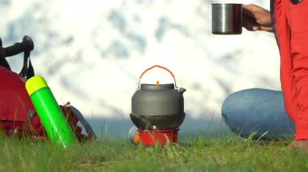 raincoat : The woman the traveler with a red backpack sits, looks at snow mountains, on the gas burner there is a teapot. The woman has tea.