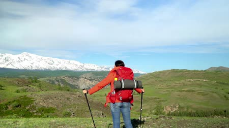 regenjas : The woman the traveler with a red backpack rises by the mountain, looks at snow mountains. Slow-motion shot.