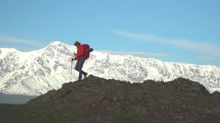 wet t shirt : The woman the traveler with a red backpack rises by the mountain, looks at snow mountains.