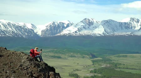 wet t shirt : The woman the traveler with a red backpack sits and looks at snow mountains.