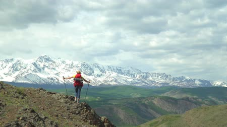raincoat : The woman the traveler in a red shirt and with a green backpack costs on the hill and looks at snow mountains. Stock Footage