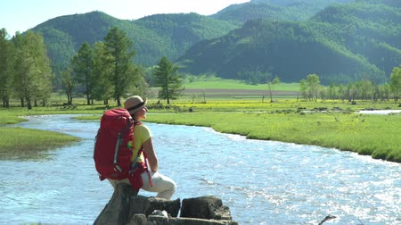 wet t shirt : The woman the traveler with a red backpack sits on the river bank. Mountain area. Stock Footage