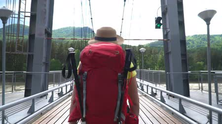 wet t shirt : The woman the traveler with a red backpack goes along the cable-stayed bridge through the mountain river.
