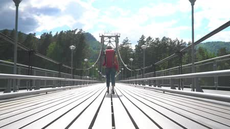 stayed : The woman the traveler with a red backpack goes along the cable-stayed bridge through the mountain river.