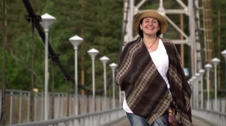 wet t shirt : The woman the traveler in a poncho and in a straw hat goes along the cable-stayed bridge through the mountain river.