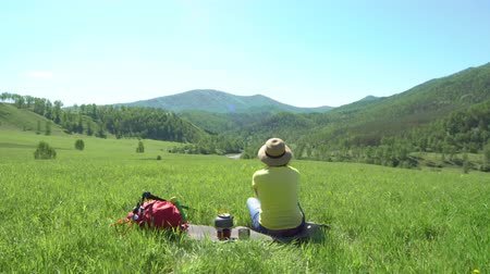 wet t shirt : The woman the traveler with tourist sticks and with a red backpack climbs down a green mountain. Then the woman sits on a grass, the teapot on the gas burner stands nearby.