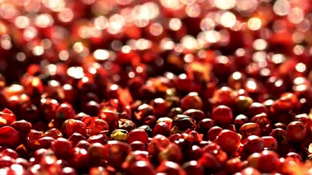 biber tanesi : Pink peppercorns placed on a kitchen table.Extreme macro of a Himalayan pepper berries.concept of fresh and dietary spices for cooking schools and vegans and dietary products.Вращение.