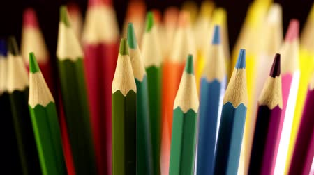 Top of color pencils. Color pencils turning on a black background. Close up. 4K footage. on a black background in a glass there are multi-colored pencils. Bright colored pencils.Color pencils turning on a black background.Beautiful view.