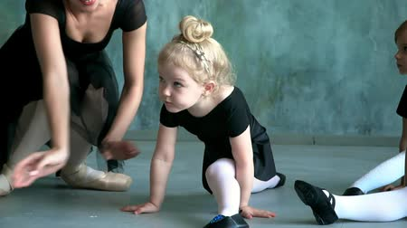 Girl dancer in ballet school learns to dance. Little Ballerina in training in black dancing suit. Childrens ballet school.